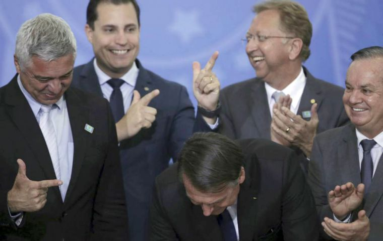 Beaming members of Congress and industry lobbyists clapped and made pistol signs with their hands as Bolsonaro relaxed rules on weapons