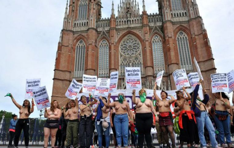 "Shirtless women, calling the protest a ""tetazo,"" or ""boob-protest"", shouted slogans: ""Abort your heterosexuality,"" ""'death to the macho' is not a metaphor."""