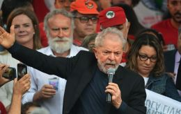 Lula wearing a black T-shirt and suit jacket, pumped his fist in the air as he exited the federal police HQ in Curitiba and was mobbed by hundreds of supporters