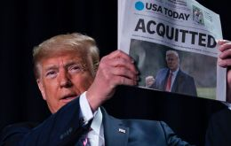 Trump made his feelings clear by holding up a copy of USA Today with another banner headline proclaiming his acquittal.