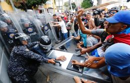 Opposition protesters face the police that block their march in Caracas on Tuesday. (AP Photo / Ariana Cubillos)