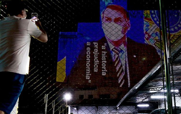 "A signboard with the figure of Jair Bolsonaro and the inscription ""Hysteria hurts economy"" over him."