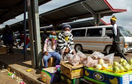 A woman and her daughter wearing face masks to protect against coronavirus, sell fruit and vegetables at the taxi station in Lenasia, south of Johannesburg, South Africa. AP PHOTO/THEMBA HADEBE