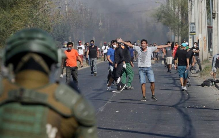 A group of protesters threw rocks, shouted and burned piles of wood along a street in the destitute neighborhood on Santiago's southern fringe
