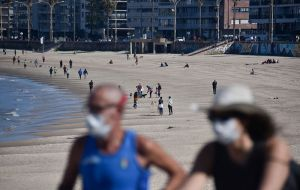 A balmy sunny weekend along the Uruguayan coast with people enjoying the good weather using face masks