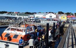 Cruise tourists landing in Stanley pier during a busy sunny summer day