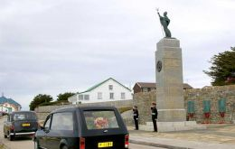 As it passes the 1982 Liberation Monument, the hearse carrying Mr Peck's coffin is saluted by Privates Craig Paice and Zoran Zuvic of the Falkland Islands Defence Force.